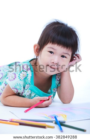 Pretty asian girl lie on the floor looking at camera. Concepts of creativity and education, strengthen the imagination of child. Studio shot. On white background. - stock photo