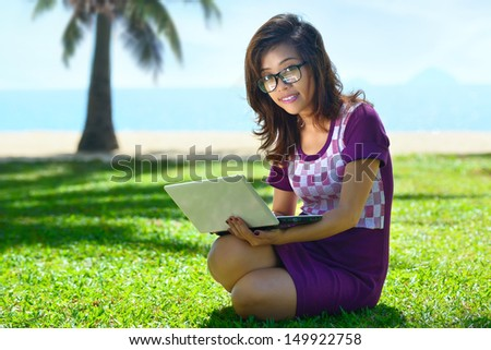 Pretty Asian girl sitting with a laptop in the park on the grass against the sea.
