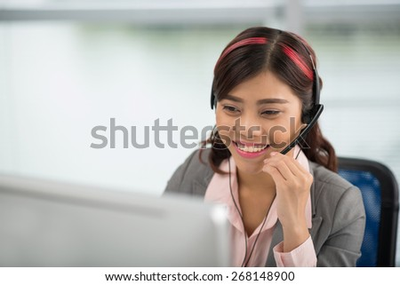 Pretty Asian help desk manager in a headset - stock photo
