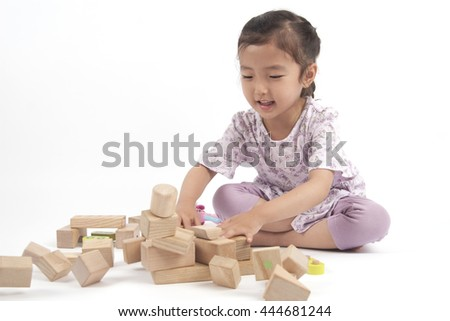 pretty asian little girl playing some blocks happily
