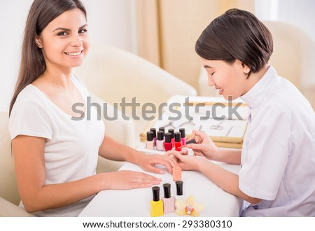 Pretty asian manicurist applying nail polish to client. Hands care concept. - stock photo