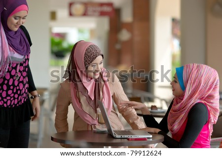 Pretty Asian Muslim college girls meeting friends at coffee shop
