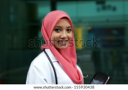 Pretty asian muslim woman doctor smile while holding tablet device - stock photo