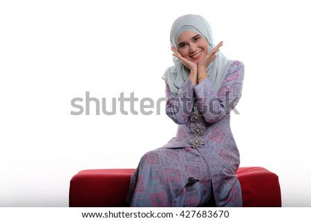 Pretty asian muslim woman wearing traditional malay costume known as songket is smiling and making pretty face while sitting on red sofa on white background  - stock photo