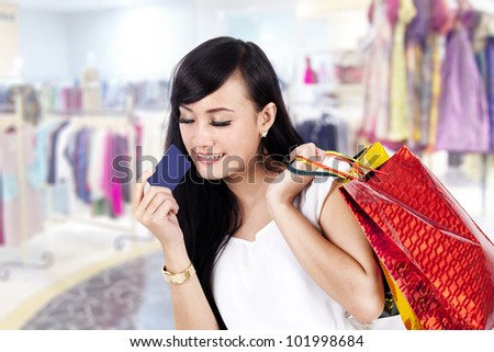 Pretty Asian woman carrying her shopping bag and a credit card ready to shop some more - stock photo
