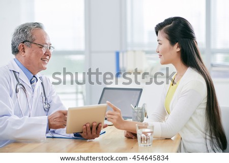 Pretty Asian woman having appointment with her doctor