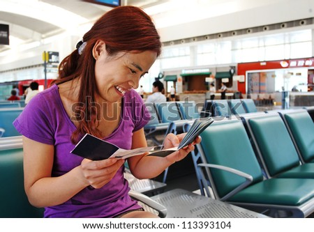 Pretty Asian Woman  in the Airport Checking her Passport and Boarding Pass - stock photo