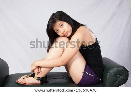 Pretty Asian woman sitting in tank top  and looking at the camera with her cheek on her knees
