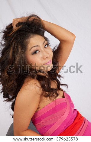 Pretty Asian woman sitting on a bench with a happy smile