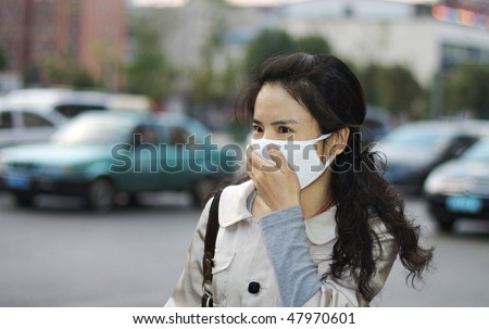 Pretty Asian woman wearing a face mask to protect against pollution or disease - stock photo