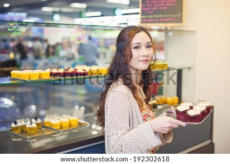 Pretty asian woman working at her own store - stock photo