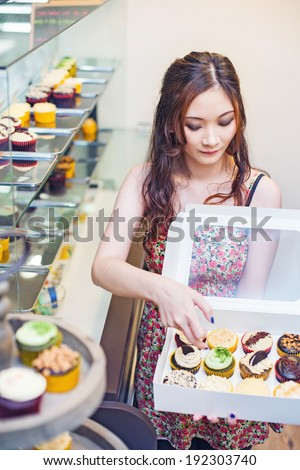 Pretty asian woman working at her own store and packing cupcakes