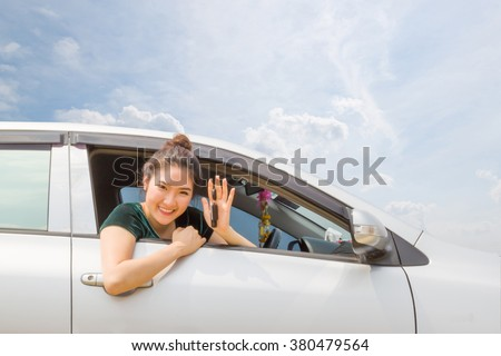 Pretty asian young woman driving her new car - stock photo