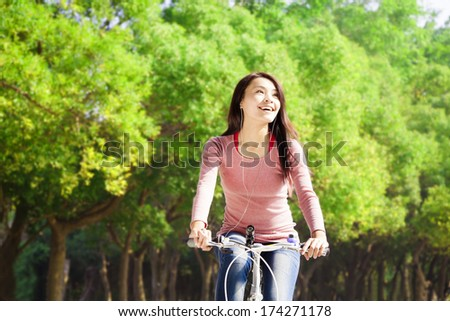 Pretty asian young woman riding bike in the park - stock photo