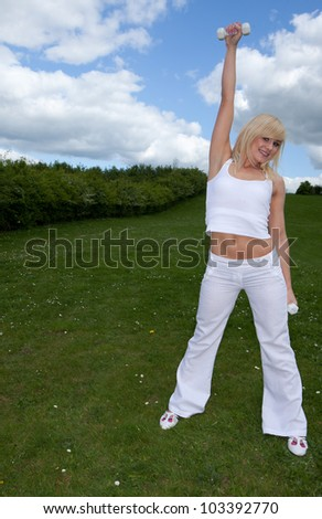 Pretty athletic blonde female with her arm raised working out with dumbbells in a lush green field - stock photo
