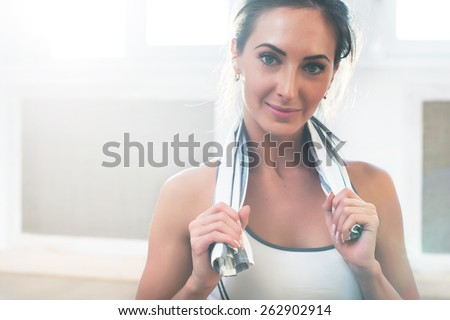 Pretty athletic sporty girls is smiling holding a towel after the training and looking at camera - stock photo
