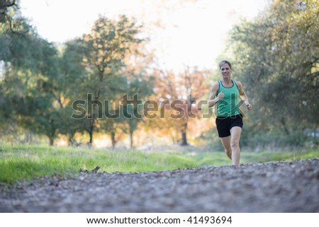 Pretty Athletic Woman Running in a Park