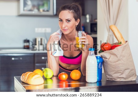 Pretty attractive athletic active sportive lady woman standing in kitchen with a towel on her shoulder and healthy food fresh fruits milk bread drinking juice. - stock photo