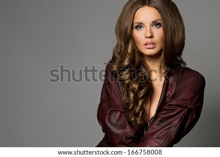Pretty attractive erotic brunette woman in maroon jacket, grey background