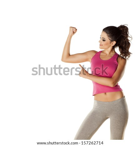 pretty attractive girl shows her  biceps with finger - stock photo