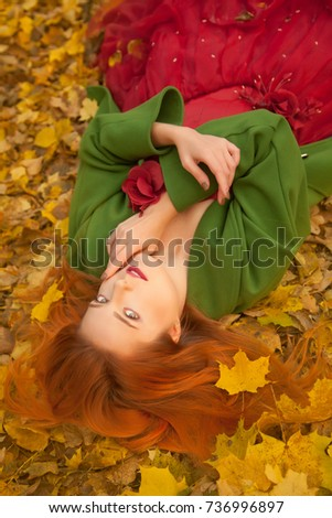 pretty autumn girl with red hair in the yellow park alone