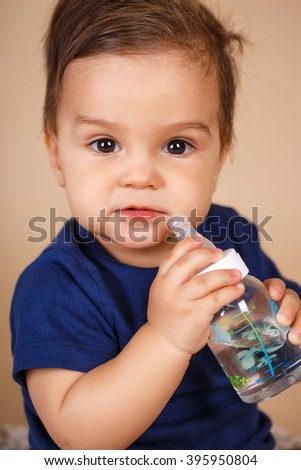 Pretty baby drinks water from bottle lying on bed. Child weared diaper in nursery room. baby holding bottle and drinking water. sweet funny baby drinking water