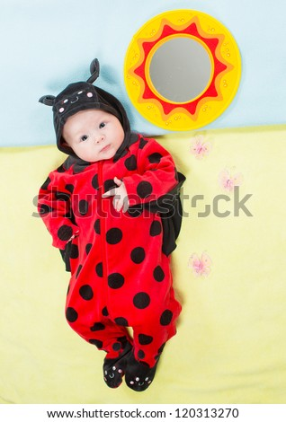 Pretty baby girl, dressed in ladybug costume on green background  The concept of childhood and holiday - stock photo