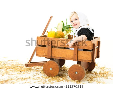 pretty baby girl dressed in pilgrim costume sitting in a wagon with her harvest produce - stock photo