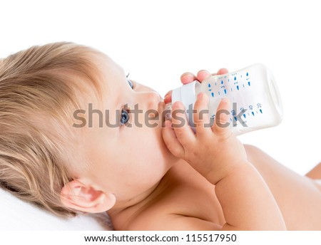 Pretty baby girl drinking milk from bottle - stock photo