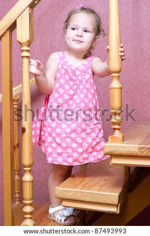 Pretty baby girl in a pink dress up the stairs in the house