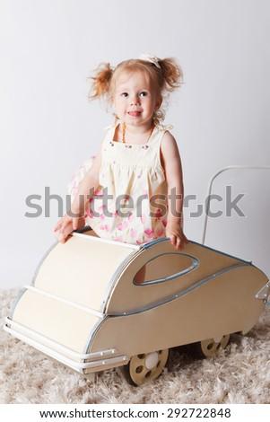 Pretty baby girl in a retro pram - stock photo
