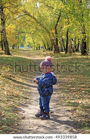 Pretty baby girl in pink striped cap and blue jacket walking in autumn park