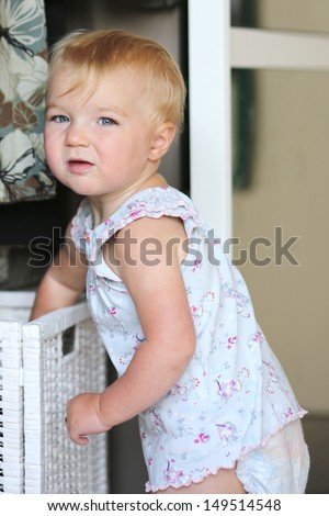 Pretty baby girl is standing in front of the opened wardrobe searching for clothes in a white storage basket - stock photo