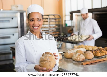 Pretty baker smiling at camera with loaf in the kitchen of the bakery - stock photo