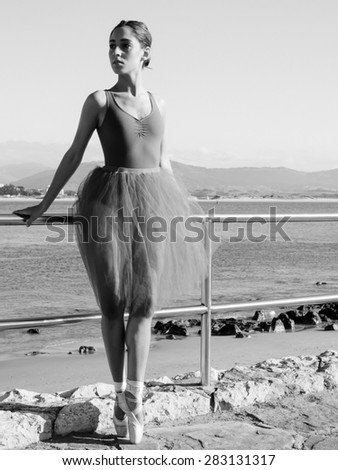 Pretty ballerina on black &  white image with sea at background