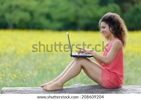 Pretty barefoot woman with frizzy curly hair wearing a trendy miniskirt sitting on a fallen tree trunk in a rural field working on a laptop and looking at the camera with a friendly smile