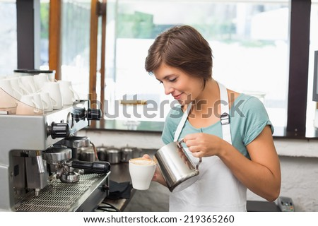 Pretty barista pouring milk into cup of coffee at the coffee shop - stock photo