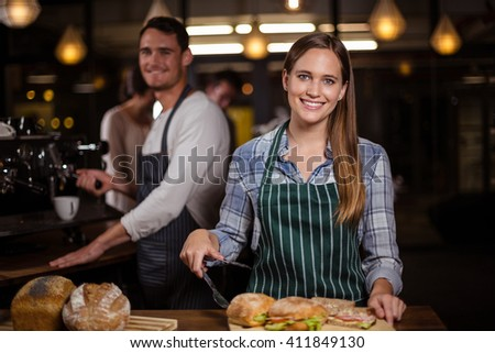 Pretty barista smiling at camera at the cafe