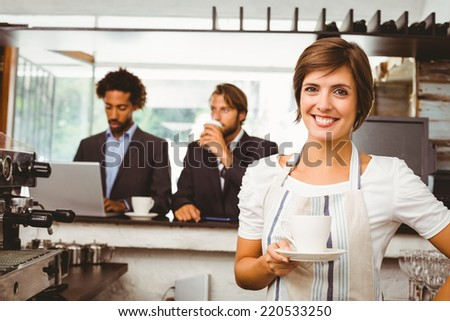Pretty barista smiling at camera at the coffee shop - stock photo