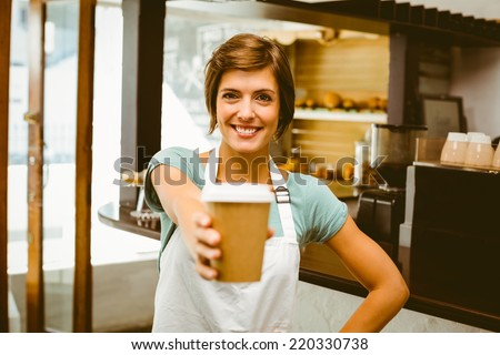 Pretty barista smiling at camera holding disposable cup at the coffee shop - stock photo