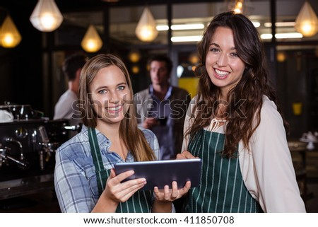 Pretty baristas using tablet in the bar
