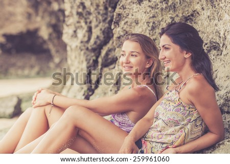 Pretty beautiful brunette and blonde girl friends having fun. Both sitting on the beach and smiling (laughing). Concept of female friendship. - stock photo