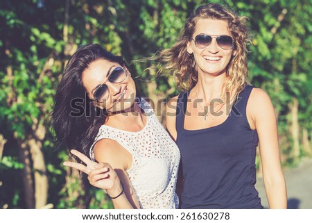 Pretty beautiful brunette and blonde girl friends in sunglasses having fun. Both looking at camera and smiling (laughing). Concept of female friendship. - stock photo