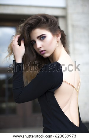 Pretty beautiful business woman in elegant black dress against city background.