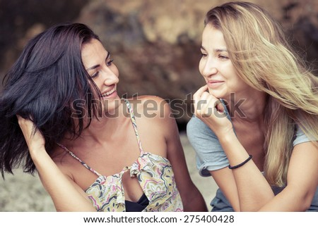 Pretty beautiful girl friends  having fun. Both looking at camera and smiling (laughing). Concept of female friendship. - stock photo
