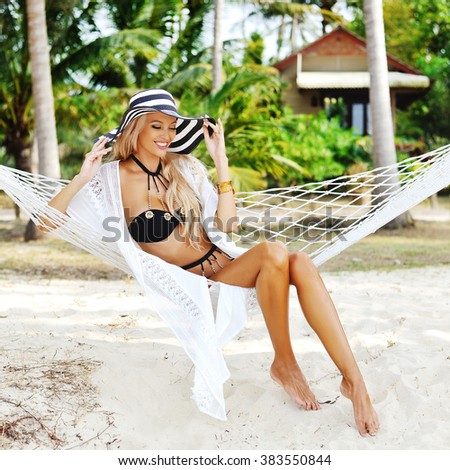 Pretty beautiful girl relaxing in hammock on a beach - stock photo
