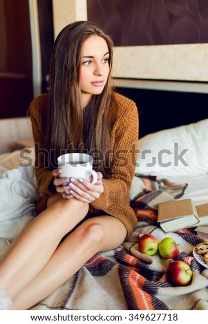 Pretty  beautiful  woman  with long hairs   enjoying morning time , eating  apples and cookies, drinking tea or coffee , warm cozy colors. Fall or winter time  concept.  - stock photo