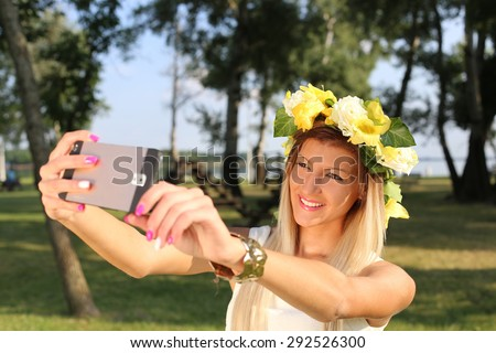 pretty beautiful young woman taking selfie photo with her mobile phone in a park - stock photo