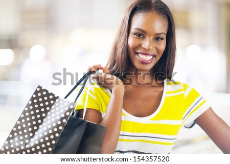 pretty black lady shopping in mall - stock photo