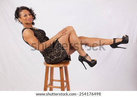 Pretty Black woman balanced on a stool and kicking up her legs